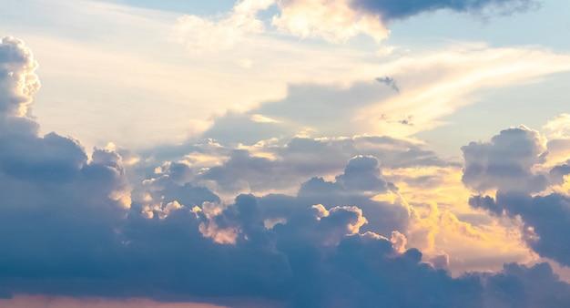 Panorama van blauwe hemel met pluizige wolken bij zonsondergang