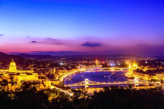 Panorama van boedapest met het parlement en bruggen tijdens blauwe uurzonsondergang.