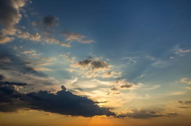 Panorama van de hemel bij zonsopgang of zonsondergang. prachtig uitzicht op donkerblauwe wolken verlicht door fel oranjegele zon op heldere hemel. schoonheid en kracht van de natuur, meteorologie en klimaatveranderend concept.