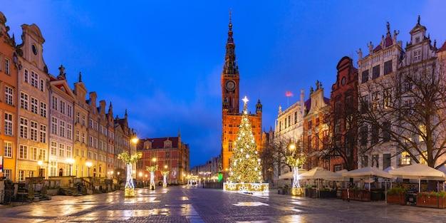 Panorama van de kerstboom en verlichting op long market street en het stadhuis 's nachts in de oude binnenstad van gdansk