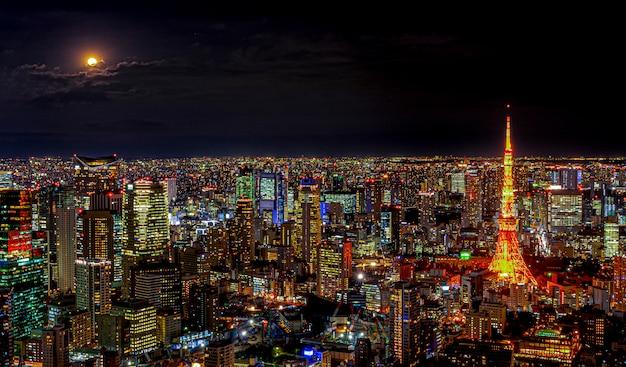 Panorama van de moderne stad met verlichting van architectuur die onder nachthorizon bouwen en lichte volle maan en wolk in de stad van tokyo, japan.