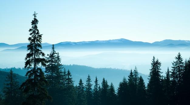 Panorama van de winterheuvels en vallei die met sneeuw en witte rook wordt behandeld