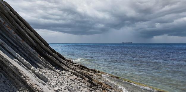 Panorama van een bewolkt zeegezicht. een pittoresk stenen wild strand aan de voet van de rotsen bij regenachtig weer