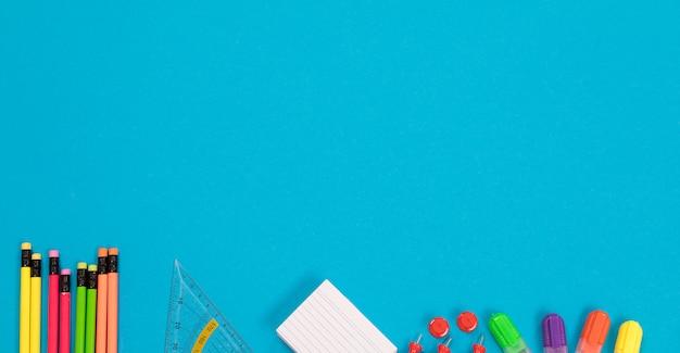 Panorama van een half zichtbare veelkleurige potloden, driehoekige liniaal, stapel wit kladpapier, een groep rode pushpins, vier kleurrijke markeerstiften liggen van een lichtblauw geïsoleerd oppervlak