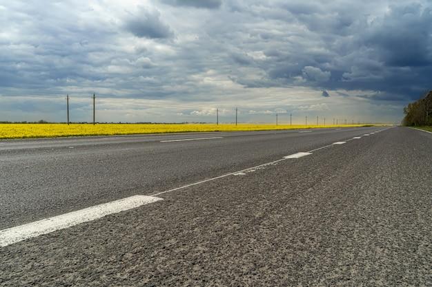 Panorama van een weg met donkere regenwolken