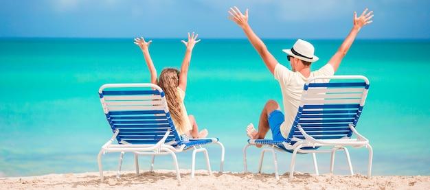 Panorama van familie van vader en kind handen omhoog op strand zittend op chaise-longue