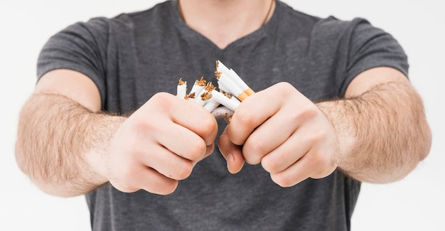 Panorama van glimlachende mensen brekende sigaretten met twee handen