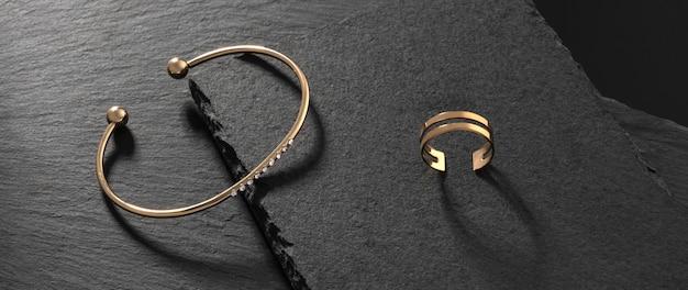 Panorama van gouden met diamanten moderne armband en dubbele vormring op zwarte stenen dienbladen