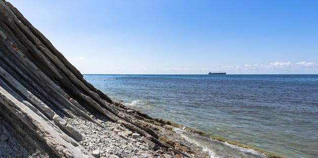 Panorama van het zeegezicht. pittoresk stenen wild strand aan de voet van de kliffen, helderblauwe lucht met wolken en een schip aan de horizon. omgeving van de badplaats gelendzhik. rusland, zwarte zee