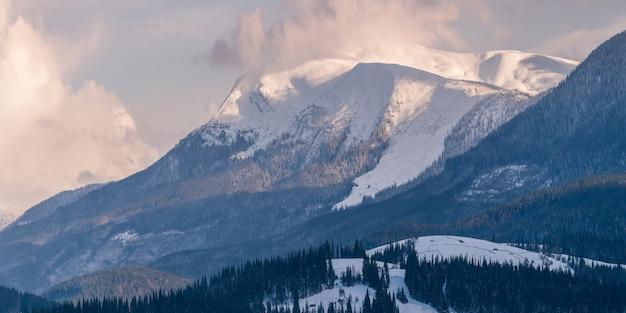 Panorama van hoge besneeuwde bergen die zich uitstrekken in de lucht met wolken
