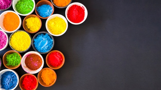 Panorama van holi kleurenpoeder in de kommen op zwarte achtergrond