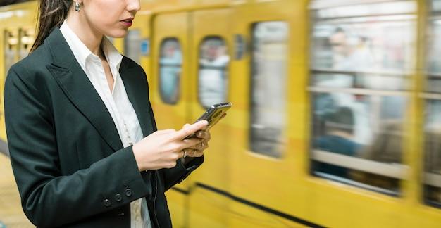 Panorama van jonge onderneemster die mobiele telefoon met behulp van die zich dichtbij de metrotrein bevindt