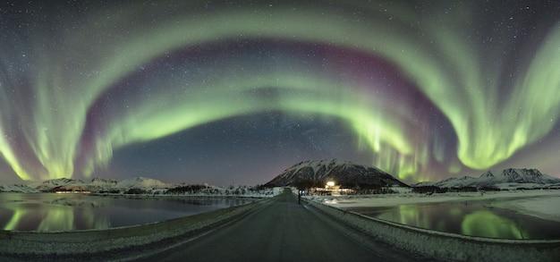Panorama van kleuren die een gewelf creëren over een brug, omringd door een winterwonderland