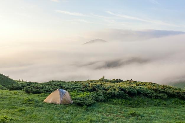Panorama van koude mistige de zomerochtend en toeristische wandelaarstent in karpatische bergen