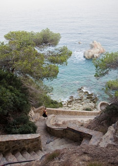 Panorama van mooie rotsen trappen in lloret de mar en aantrekkelijke jonge vrouw beneden lopen in zwarte jurk op zoek op een zee. meisje die beneden tegen rollende overzees en rotsen in spanje lopen.