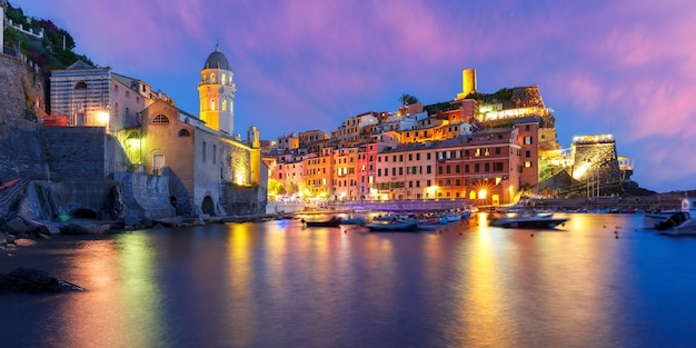 Panorama van nacht vissersdorp vernazza met santa margherita di antiochia kerk en uitkijktoren van doria castle, five lands, cinque terre national park, ligurië, italië.