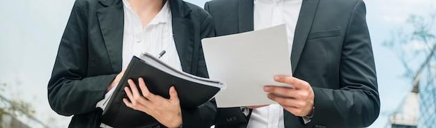 Panorama van onderneemster en zakenmanholdingsdocumenten in de handen