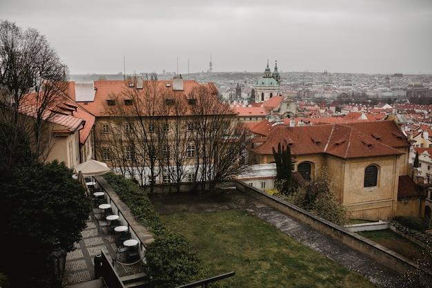 Panorama van praag met rode daken en kerk. uitzicht op de stad van de oude stad van praag. rustiek grijze tinten.