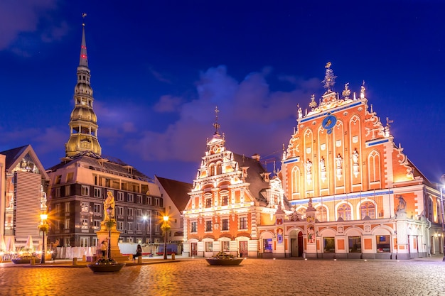Panorama van riga old town hall square, roland statue, the blackheads house en st peters cathedral verlicht in de schemering, riga, letland