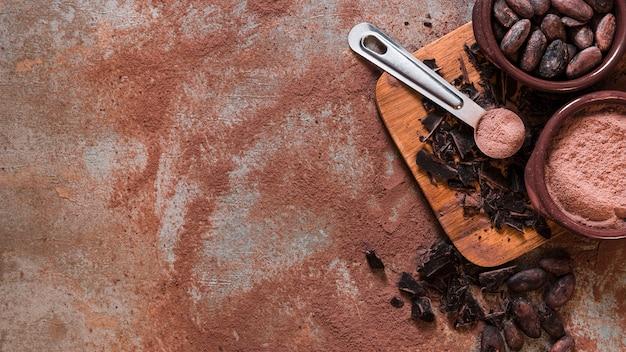 Panorama van verpletterde chocolade en cacaobonen en poederkom