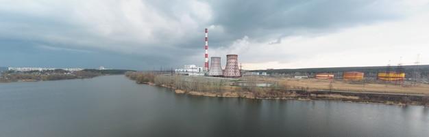 Panorama van waterkrachtcentrale aan de oever van de rivier in bewolkt weer