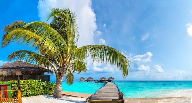 Panorama van watervilla's en houten brug in tropisch strand