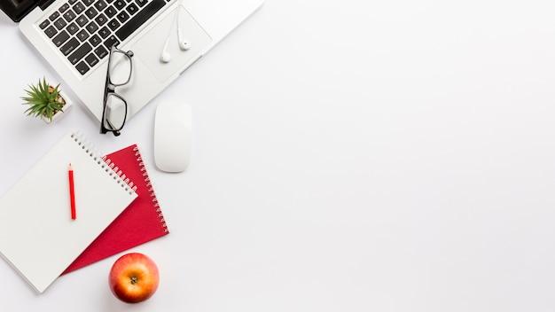 Panorama van wit bureau met laptop, appel en kantoorbenodigdheden