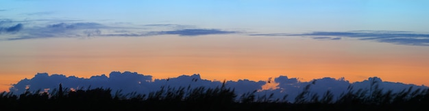 Panorama van wolken en oranje zonsondergang