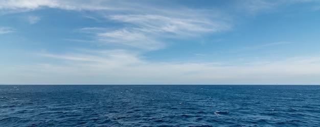 Panorama van zee met kleine golven en schuim en lucht met witte wolken