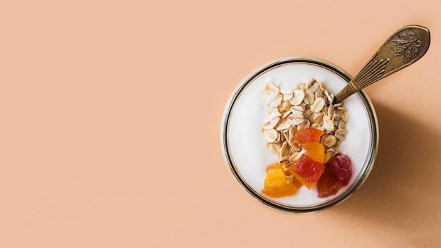 Panorama van zure roomyoghurt met haver en vruchten die in de kruik bedekken
