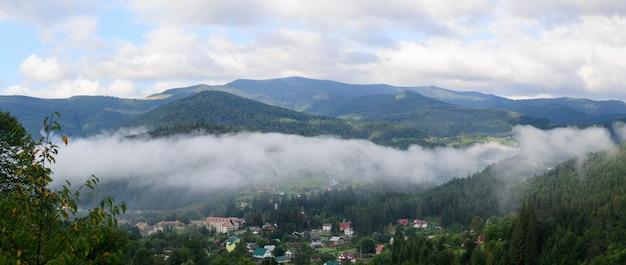 Panoramadorp in de bergen met het nevelige boslandschap dat van de wolkenochtend wordt behandeld