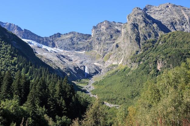 Panoramamening van bergenscènes in nationaal park dombay, kaukasus, rusland, europa. zomerlandschapsdag en zonnige blauwe lucht