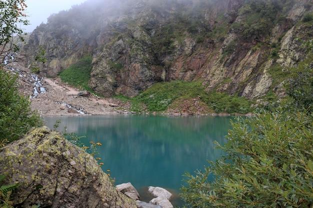 Panoramamening van meerscène in bergen, nationaal park van dombay, kaukasus, rusland. zomerlandschap, zonneschijn, dramatische blauwe lucht en zonnige dag