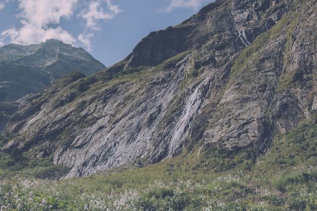 Panoramamening van watervalscène in bergen, nationaal park van dombay, kaukasus, rusland. zomerlandschap, zonneschijn, dramatische blauwe lucht en zonnige dag