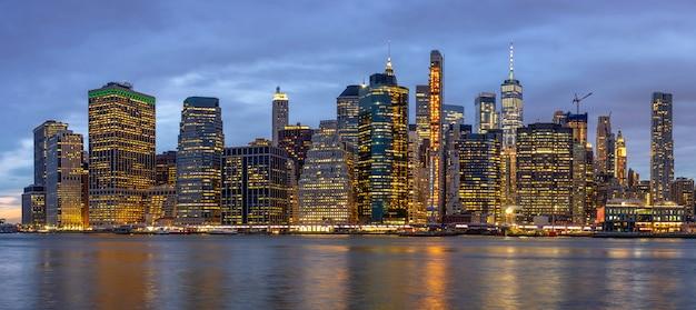 Panoramascène van cityscape van new york met de brug van brooklyn naast de rivier van het oosten in de schemeringtijd