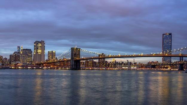 Panoramascène van de brug van brooklyn naast de rivier van het oosten met cityscape van new york in de schemeringtijd