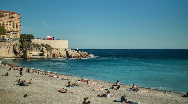Panoramisch beeld van de mooie kustlijn met het strand en de kliffen en de blauwe zee op de achtergrond tot aan de horizon.
