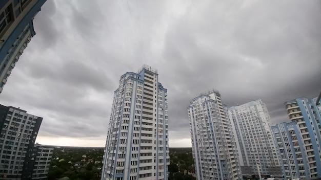 Panoramisch beeld van donkere lucht bedekt met grijze en zwarte regenwolken boven hoog levend gebouw in de stad. stadsgezicht voor de storm