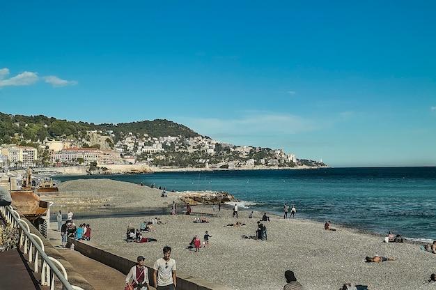 Panoramisch beeld van het mooie strand met mensen die zonnebaden op het kiezelstrand voor een ongeëvenaard panorama.