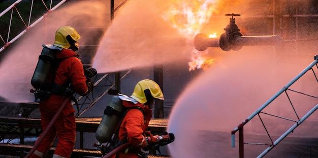 Panoramisch brandweermansteam gebruikt watermist-type brandblusser om met vlammen te vechten