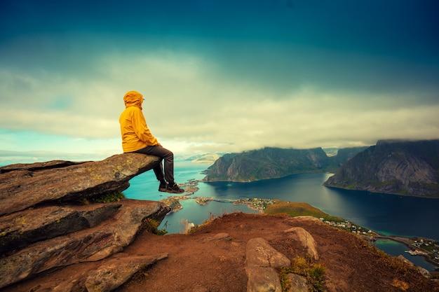 Panoramisch luchtfoto van fjord en vissersdorp. man toeristische zittend op een klif van rots. prachtig berglandschap. natuur noorwegen, lofoten eilanden.