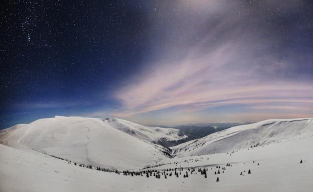 Panoramisch nachtzicht van winter bergdal bedekt met sneeuw, bergen en maan