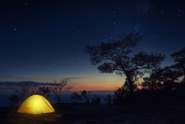 Panoramisch natuurbeeld van verlichte gele campingtent met melkweg en sterrennacht