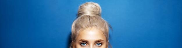 Panoramisch portret van het hoofd van de vrouw met blauwe ogen, blond haar gewikkeld in een knot, op achtergrond van fantoomblauwe kleur.