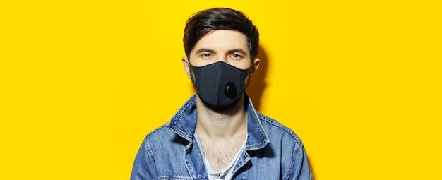 Panoramisch portret van jonge kerel met beschermend medisch gezichtsmasker tegen coronavirus en covid-19