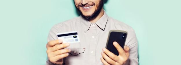 Panoramisch portret van jonge lachende man met behulp van smartphone en creditcard op cyaan achtergrond.