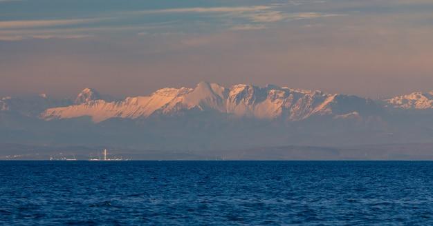Panoramisch schot van de adriatische zee in kroatië tijdens de zonsondergang en de alpen op de achtergrond