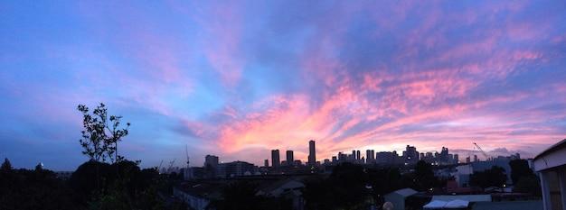 Panoramisch schot van de stadsbouw onder een purpere en blauwe hemel