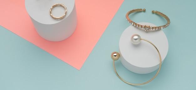 Panoramisch schot van twee gouden armbanden en ring op roze en blauwe muur
