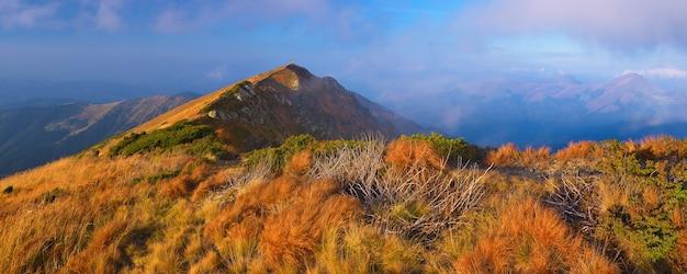Panoramisch uitzicht op de bergen. herfst landschap met bergtop en droog gras op de hellingen van de heuvel.